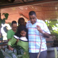 An image taken from a mobile phone of Councillor Terry Rondon, assisting Bissoondaye Seenath shorty after she was rescued at Matura yesterday.