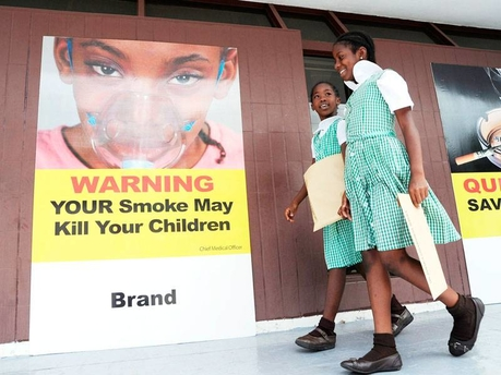 Students of St George's Girls' Primary and Infant School walk by a sign placed near the entrance to Gordon House by the Ministry of Health yesterday. The health ministry, in collaboration with the Jamaica Cancer Society and the National Council on Drug Abuse, set up an exhibition outside Parliament with a focus on cancer and the cessation of tobacco use to coincide with a Sectoral Debate contribution from Health Minister Dr Fenton Ferguson.