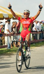 National cyclist, Alonzo Greaves, raises his hand in victory after powering to his ninth signature win of the season yesterday at the Seawall Bandstand. (Orlando Charles photo)