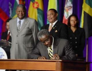 """Prime Minister Freundel Stuart signing the """"Treaty of Chaguaramas"""" yesterday. (Trinidad Express photo)"""