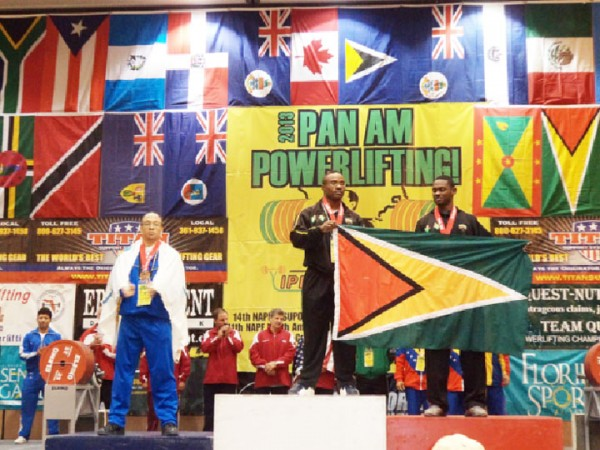 Randolph Morgan (centre) and Anis Ade Thomas holding the Golden Arrowhead yesterday after finishing first and second respectively in the 83kgs Men class of the Caribbean Powerlifting Championships.