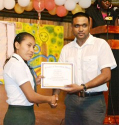 Sylvia Alexander, of Region 9 receives her certificate from Ministry of Amerindian Affairs' Permanent Secretary Nigel Dharamlall at the Hinterland Scholarship Programme graduation at the Amerindian Village, Sophia on Wednesday. (Government Information Agency photo)