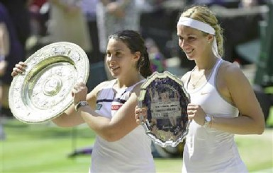 Marion Bartoli of France (L) holds her trophy, the Venus Rosewater Dish, after defeating Sabine Lisicki of Germany (R) in their women's singles final tennis match at the Wimbledon Tennis Championships, in London July 6, 2013. (Reuters/Toby Melville).