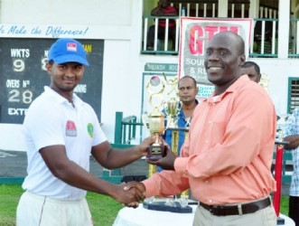 Man of the match in the finals for his century, Brian Sattaur receiving his trophy from match referee, Colin Stuart.