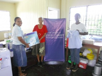 From left: Marcia McKenzie, Eugene Lewis and Mrs Young, a community member with some the donated items