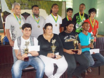 The winners of the Trophy Stall Chess Tournament display their trophies starting with, from left seated, Roberto Neto, Maria Thomas, Taffin Khan and Anthony Drayton. In the back row, from left, Raymond Singh, Ron Motilall, Carlos Petterson, Rajiv Muneshwer, Omar Britton-Grant and Haifeng Su.