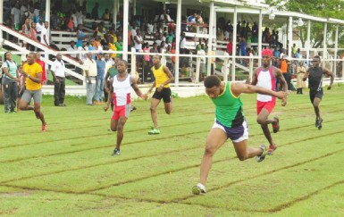 Kevin Abbensetts (right) dips at the 100m finish line in the Youth Club boys' 100m heats yesterday afternoon ahead of sprint sensation Tevin Garraway (second left). (Orlando Charles photo)