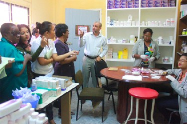 Hospital Director Kevin Mana speaking with members of the visiting Parliamentary Sector Committee on Social Services inside the pharmacy, where employees were busy at work packaging pills. (Photo by Arian Browne)