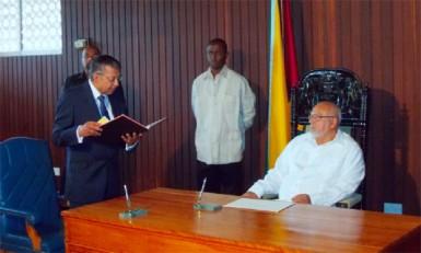 Justice Rabi Shankar Sukul (left) taking the Oath yesterday as President Donald Ramotar looks on.