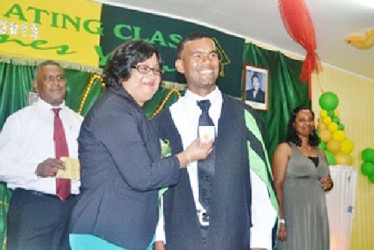 Alwyn Seegolam receives his gold medal from  Lalita Baksh. He attained a Distinction in the Diploma in Agriculture programme at the Essequibo campus. (GINA photo)