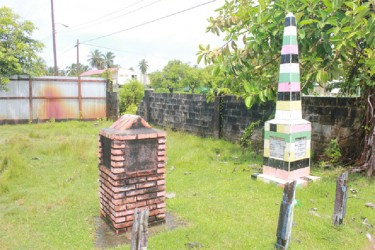 Two monuments standing in the compound of the Victoria Culture Centre; the larger of the two is in honour of the 83 former slaves who bought the village and whose names it records. (Arian Browne photo)
