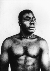 A member of the Kru nation from what is now Sierra Leone.  Some of the Kru who came here in the 19th century, gravitated to piloting boats on the hinterland rivers. They were comfortable on water, given their long experience of serving with the Royal Navy.