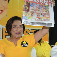 Prime Minister Kamla Persad-Bissessar holds up a copy of yesterday's Express during the United National Congress' (UNC) Monday night forum last night at the Warrenville Regional Complex in Cunupia.