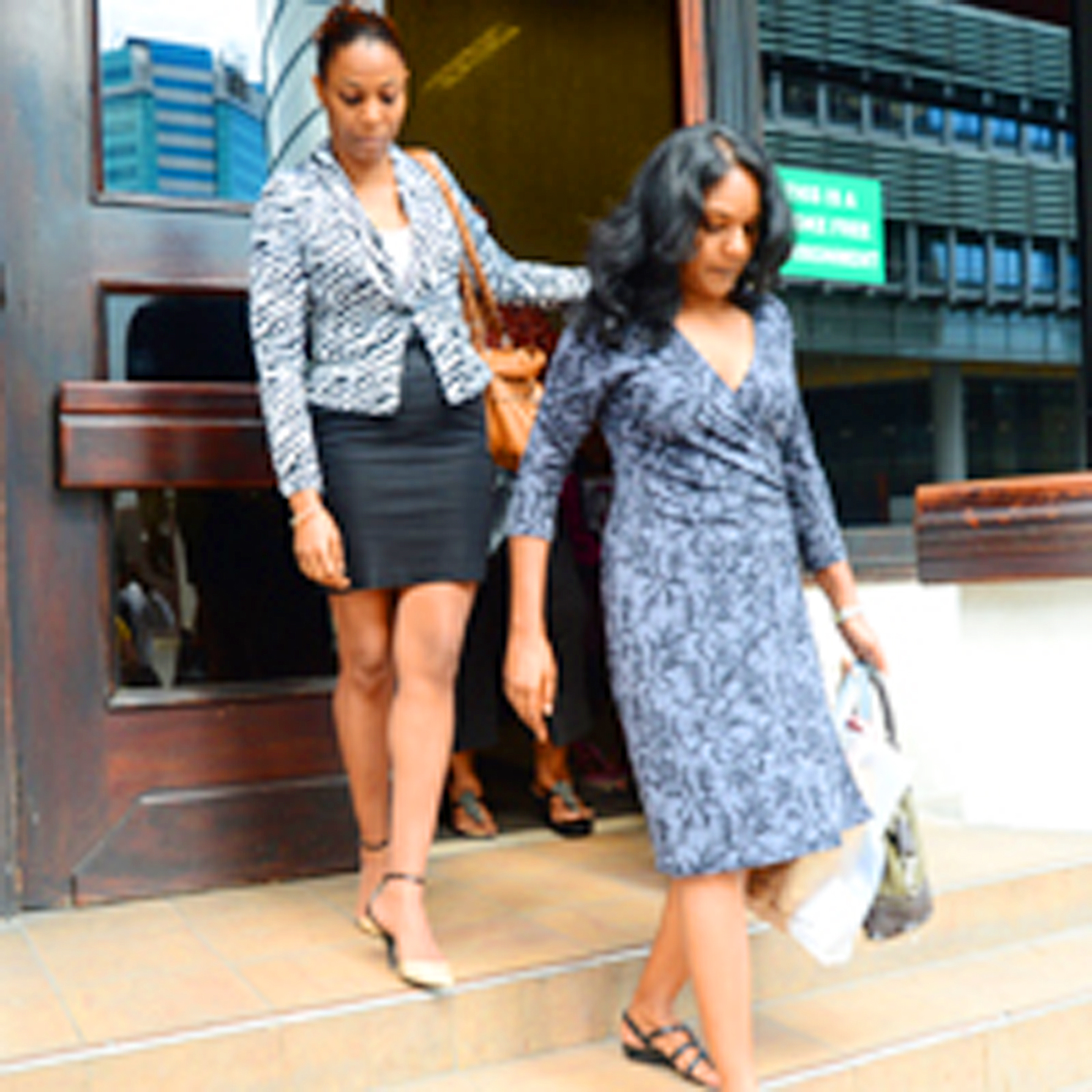 Guardian Public Affairs editor Dr Sheila Rampersad, right, and investigative reporter Anika Gumbs-Sandiford leave their offices on St Vincent Street, Port of Spain, yesterday after resigning.