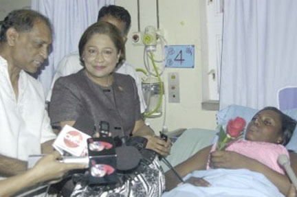 Nicolette Allen, one of the hospitalized, being visited by Prime Minister of Trinidad & Tobago Kamla Persad-Bissessar and Health Minister Dr Leslie Ramsammy. (Stabroek News file photo)