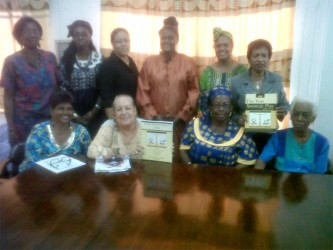Members of the Women and Gender Equality Commission along with copies of their Annual Report for 2013 and their Five Year Strategic Plan.