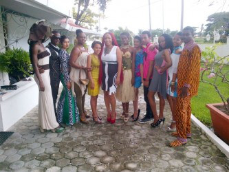 Guyana Fashion Week CEO Sonia Noel, (Center) surrounded by pieces made by some of the designers to be featured at this year's event, which will be launched on Sunday