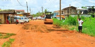 Working to patch the main access road to Kumaka which is pitted with potholes