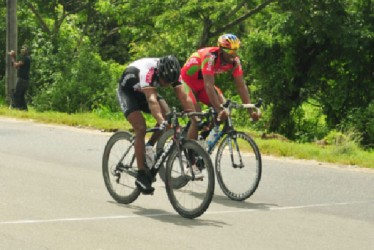 Robin Persaud edges Warren '40' McKay to take yesterday's 10th annual Regan Rodrigues 50-mile road race on the West Demerara. (Orlando Charles photo)