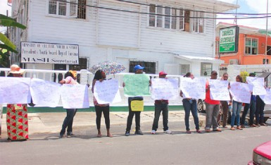 Protestors across the street from the Georgetown Magistrates' Court building on Middle Street, demonstrating against the sentencing of four policemen found guilty of assaulting businessman Nizam Khan (Photo by Arian Browne)
