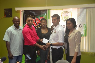 Slingerz FC Financial Director Aswell Mohabir receives the sponsorship cheque from Stag Beer Brand Manager John Maikoo while club PRO Mark Young (extreme left), NAWF President Vanessa Dickenson (centre), tournament coordinator Colin `BL' Aaron (right) and Ansa McAl PRO Darshanie Yussuf (extreme right) look on.
