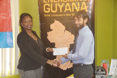 NAWF President Vanessa Dickenson receives the sponsorship cheque from Lucozade Brand Manager Sunesh Maikoo.