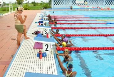 Head Coach Isabella Couso Fals pays keen attention to the swimmers during their final training session at the National Aquatic Centre yesterday afternoon. (Orlando Charles photo)