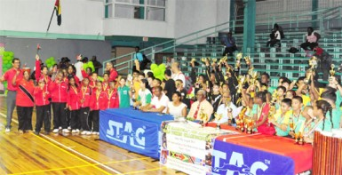 From left GTTA President Godfrey Munroe, GT&T Brand Manager Nicola Duggan, Administrator of the National Sports Commission, Gervy Harry, Director of Sports Neil Kumar and Caribbean Regional Table Tennis association President Juan Villa, surrounded by the teams from some of the participating countries.