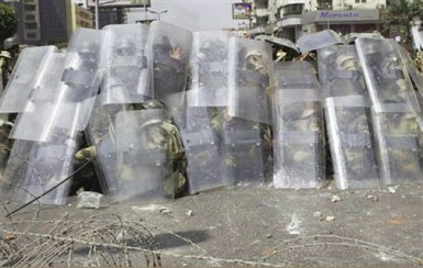 Riot police and army soldiers protect themselves with riot shields as members of the Muslim Brotherhood and supporters of ousted Egyptian President Mohamed Mursi throw stones during clashes around the area of Rabaa Adawiya square, where they are camping, in Cairo August 14, 2013. REUTERS/Asmaa Waguih