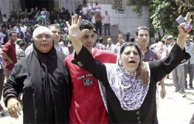 A mother holds her hands up as she escorts her son out of the  el-Fath mosque in Cairo yesterday (Reuters/Muhammad Hamed)