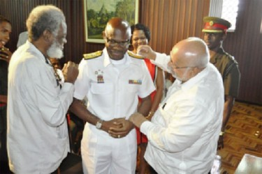 Commander- in- Chief of the Armed Forces, President Donald Ramotar (right), and Secretary of the Defence Board, Dr. Roger Luncheon pinning the insignia of the rank of Rear Admiral on Guyana Defence Force Chief  of  Staff Gary Best. (GINA photo)