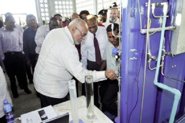 President Donald Ramotar (left) officially releasing bioethanol from the demonstration plant at Albion. (GINA photo)