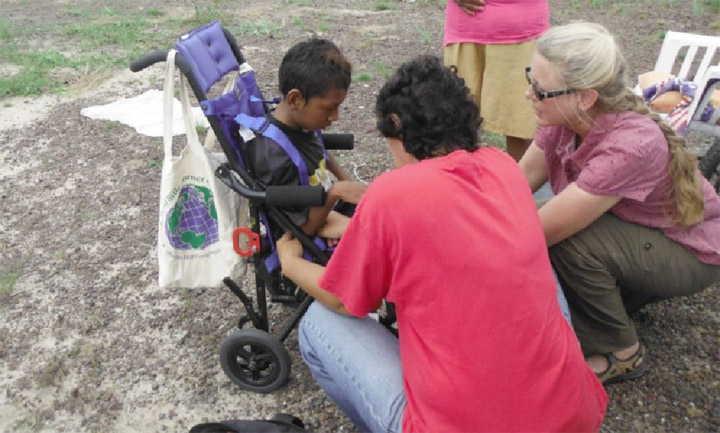 Two volunteers interact with a special needs child during the outreach