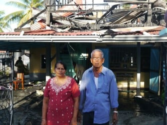 The couple stands in front of their burnt out house as relatives help to clean up (in the background)