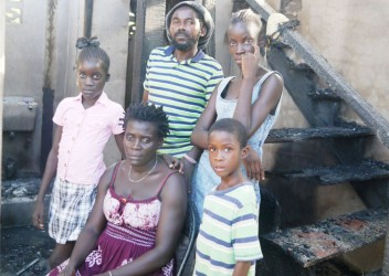 Seretse and Felicia George with their children in the burnt-out house