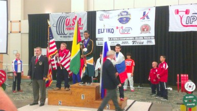 IT'S OFFICIAL! Gumendra Shewdas atop the podium is now officially Guyana's youngest ever World Champion in any sport after being crowned World Champion of the 53kg class in the IPF World Juniors and Sub Juniors Men's Championships in Killeen, Texas yesterday. The new world champion is flanked by USA's Dalton La Coe (left) and Russia's Alexei Kulakov.