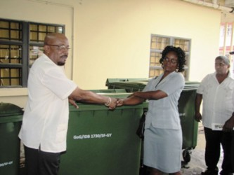 Overseer, Buxton/Foulis NDC Cherlyn Herod (second from right) uplifts the bins from Minister in the Ministry of Local Govern-ment and Regional Development Norman Whittaker. (GINA photo)