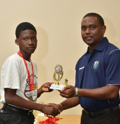Ashmead Nedd receives his trophy for Most Promising Player from Guyana from Head Coach Dwain Gill - WICB Media photo
