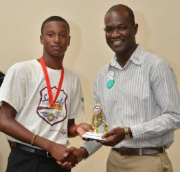 Renaldo Mohammed receives his trophy from Sandals Foundation representative OBrian Heron - WICB Media photo