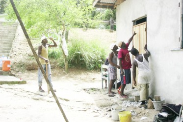 Some volunteers effecting repairs to a home in Canvas City on Sunday under the Youth Vision Home Improvement programme.