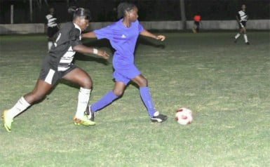 Action between the Georgetown (left) and Berbice female football teams Wednesday night at the GFC ground. (Orlando Charles photo)