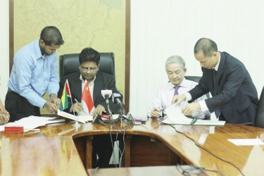 Finance Minister Dr Ashni Singh and China's Ambassador to Guyana Zhang Limin signing the agreement yesterday