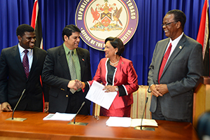 Prime Minister Kamla Persad-Bissessar shakes hands with Legal Affairs Minister Prakash Ramadhar at yesterday's post Cabinet news conference at the Prime Minister's office in St Clair yesterday. Looking on is Labour Minister Errol McLeod, right, and Minister of Tobago Development, Delmon Baker