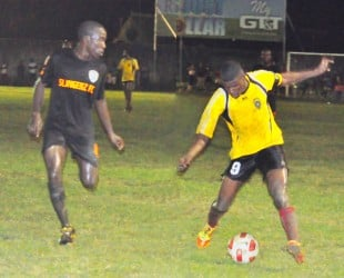 Alpha United's Dwight Peters on the right trying to keep possession of the ball against Slingerz fullback Joshua Browne