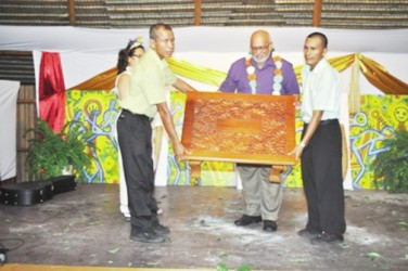 President Donald Ramotar (centre) is presented with a token at the Amerindian Heritage Month 2013 launching (GINA photo)