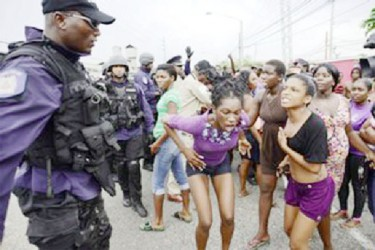 Protesters react to police officers at Beetham Gardens, Port of Spain on Monday. (Trinidad Express photo)