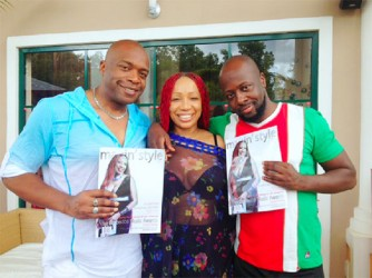 Sonia Noel standing between Haitian singer Wyclef Jean (right) and Ron Felix  promoting her magazine