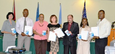 Minister of Health, Dr. Bheri Ramsaran (third from right) , representatives from PAHO, CDC and staff of the Ministry display the National Plan for Infection Prevention and Control 2012-2016 (GINA photo)