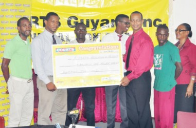 Courts Marketing Manager Pernell Cummings (second from left) presents a cheque symbolic of the $1.8M sponsorship to AAG President Aubrey Hutson while Olympian Winston George (centre), Cleveland Thomas (left), Tyshon Bentinck (second from right) and Courts PR and Marketing Officer Kester Abrams and another representative look on.