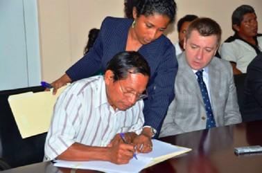 Hururu's Toshao, Winsbert Benjamin signs the lease agreement between his community and Bauxite Company of Guyana Inc., (BCGI). (GINA photo)